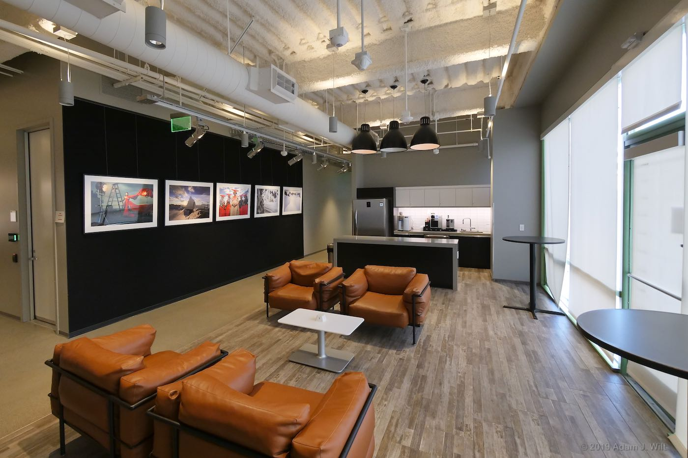 Lounge area, with EOS R photos on display. Screening room entrance on left