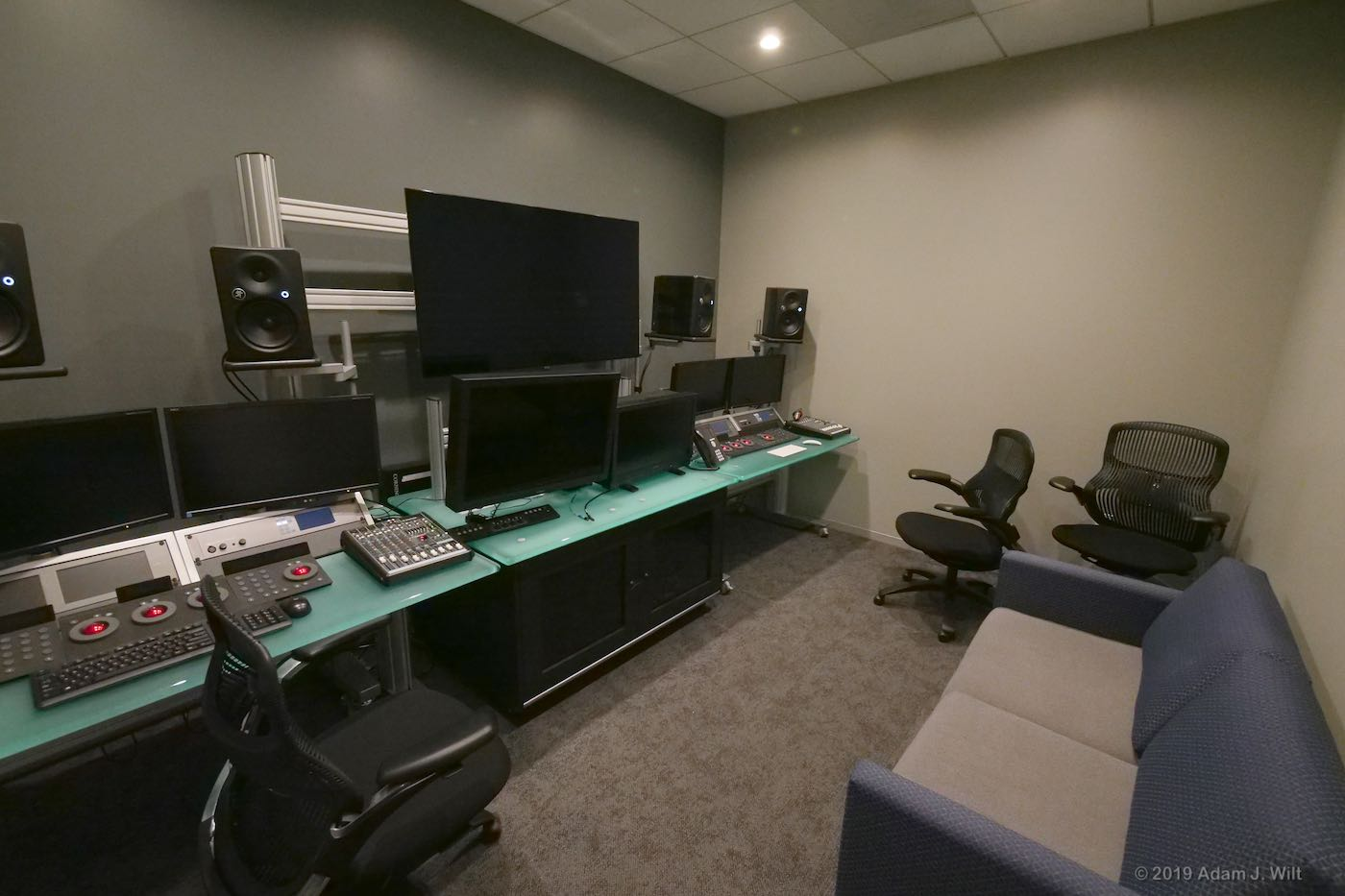 The edit bay has a client couch and two workstations: PC...