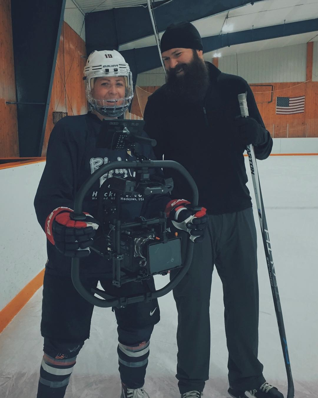 Photo of James with hockey player holding camera rig