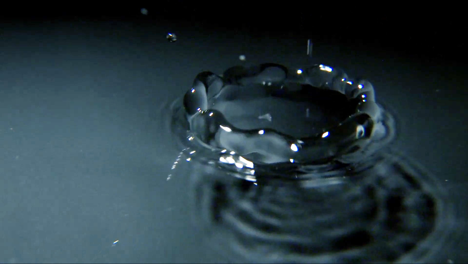 Macro photograph of a drop of water as it falls into a pool. Steel grey tones suggest a modernistic or industrial theme.