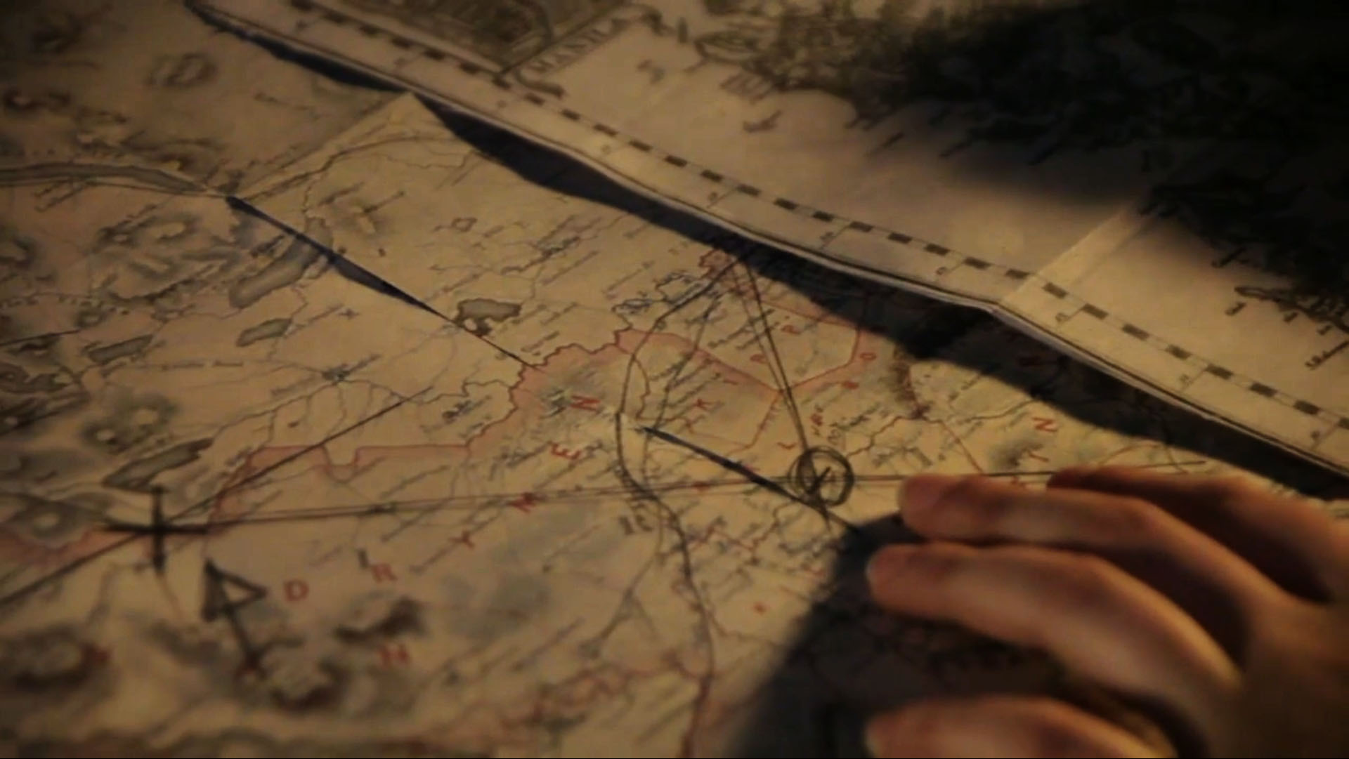 Closeup of a woman's hand as she examines an old map.