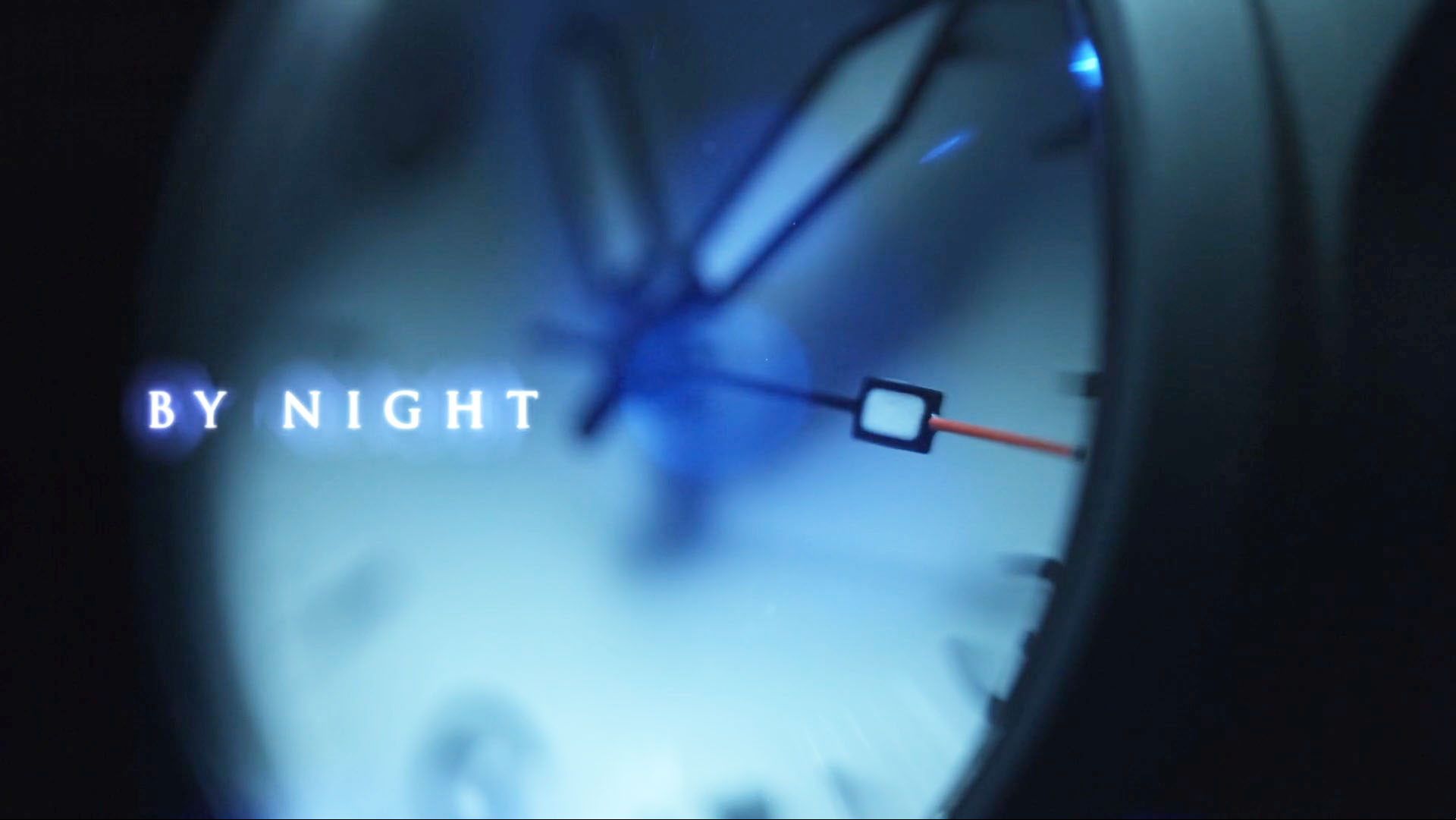 """Macro photograph of a watch face against a dark background in shades of cool blue with the text """"by night"""" superimposed."""