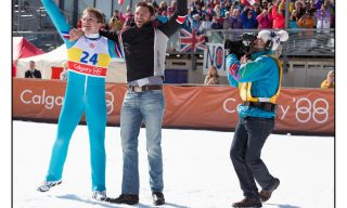 DF-01591_R - Eddie (Taron Egerton) and his coach Bronson Peary (Hugh Jackman) rejoice in Eddie's triumph.