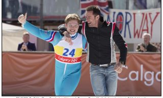 DF-01693_R - Eddie (Taron Egerton) and his coach Bronson Peary (Hugh Jackman) rejoice in Eddie's triumph.