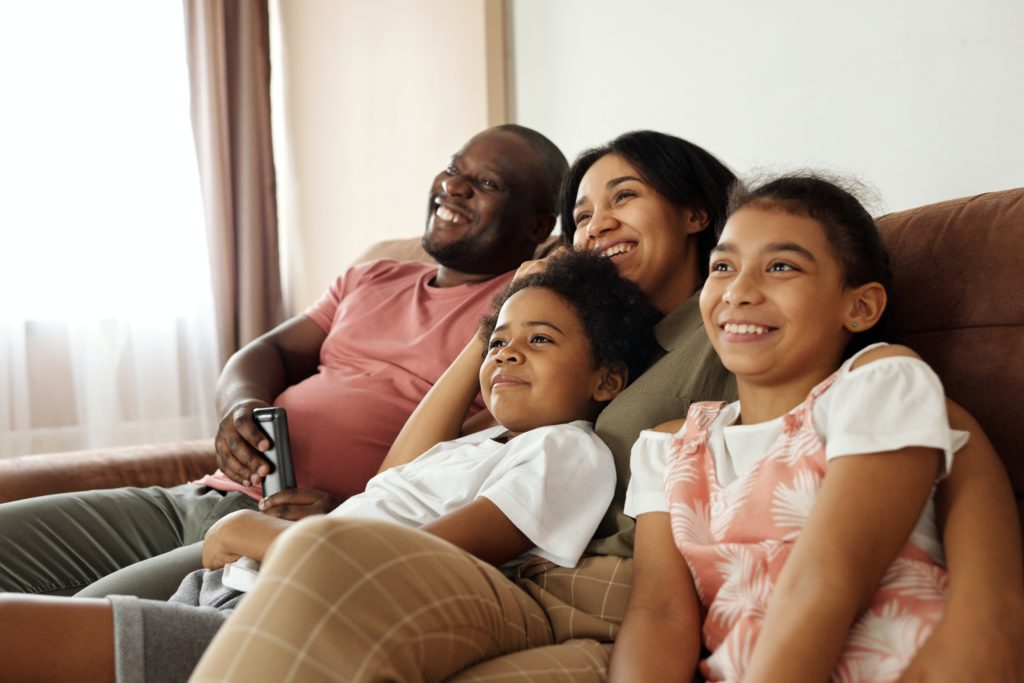 happy-family-sitting-on-a-couch-and-watching-tv-4260639