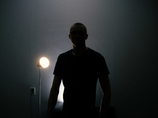 Man in a T-shirt silhouetted against a light.