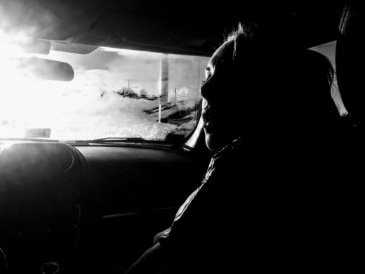 Black and white image of a woman in the passenger seat of a car, heavily backlit by the sun.