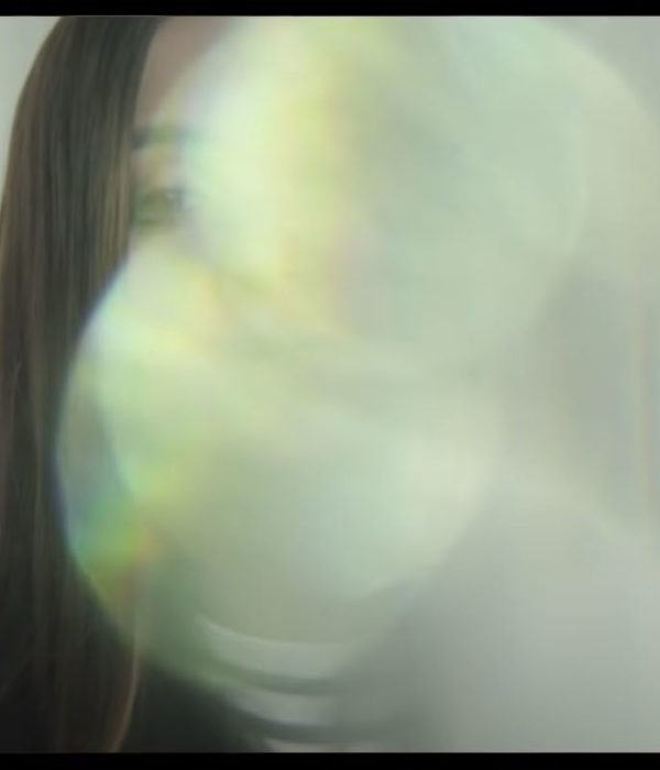 A young woman's face is almost completely obscured by a bright optical effect